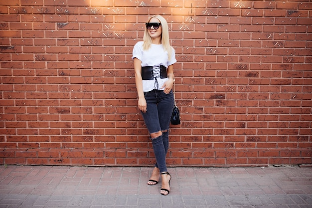 Belle femme en chemisier blanc élégant posant sur le mur de briques rouges