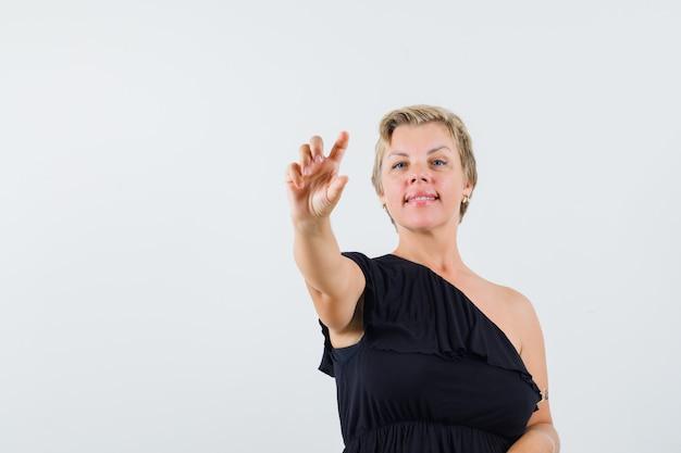Belle femme en chemisier noir posant comme montrant une bouteille de pilules