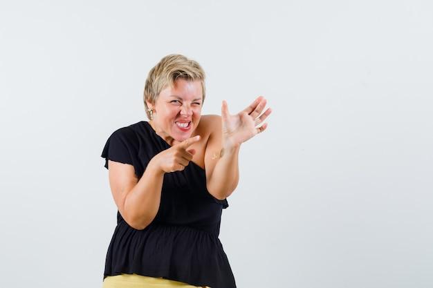 Belle femme en chemisier noir posant comme pointant sur le téléphone et à la folie