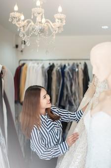 Belle femme cherche robe de mariée dans la boutique de mariage