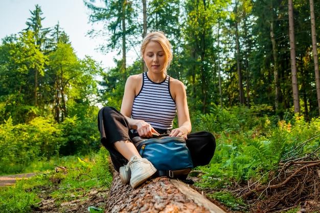 La belle femme de cheveux blonds s'assied sur la forêt de connexion