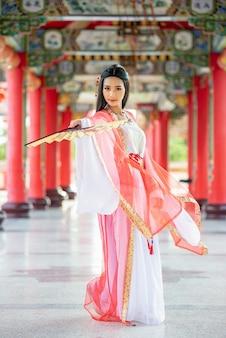 Belle femme chinoise avec un costume traditionnel avec un coup dans les mains.