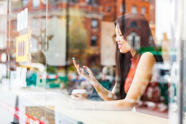 Belle femme chinoise avec smartphone dans un café