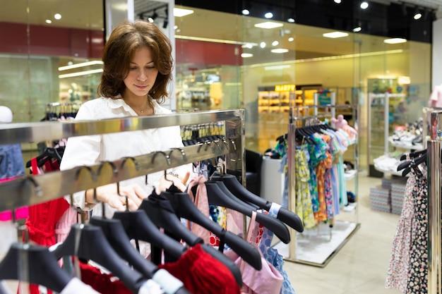 Une belle femme choisit des vêtements