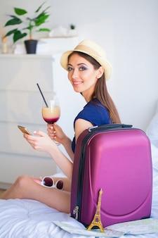 Belle femme avec cocktail et valise sur le lit dans la chambre hootel
