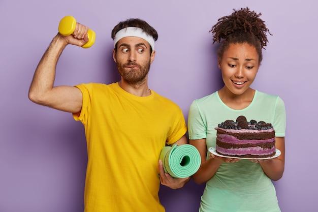 Belle femme avec une coiffure afro, tient une assiette avec un délicieux gâteau sucré