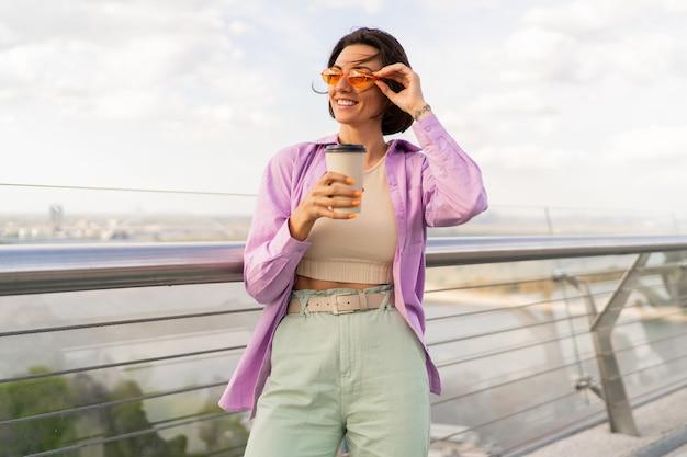 Belle femme avec une coiffure courte marchant sur un pont moderne en journée d'été venteuse