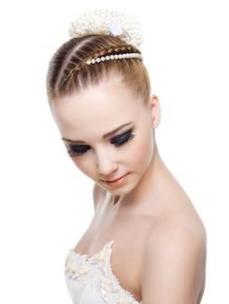 Belle femme avec une coiffure de mariage en queue de cochon.