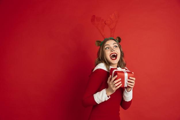 Belle femme comme le cerf de noël isolé sur le concept de mur rouge