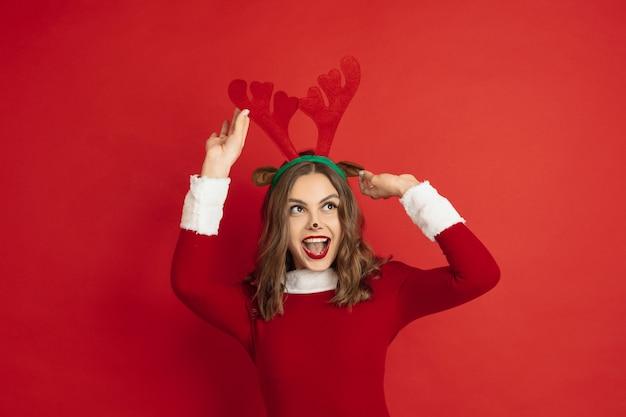 Belle femme comme le cerf de noël isolé sur le concept de surface rouge des vacances d'humeur d'hiver du nouvel an