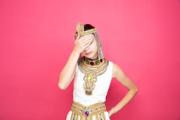 Belle femme comme cléopâtre en costume égyptien antique à la fatigue et à l'ennui couvrant les yeux avec la paume sur rose