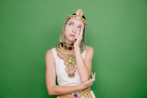Belle femme comme cléopâtre en costume égyptien antique à la recherche d'une expression pensive pensant sur le vert
