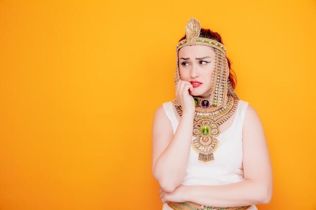 Belle femme comme cléopâtre en costume égyptien antique regardant de côté les ongles rongés stressés et nerveux sur orange