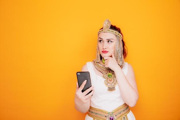 Belle femme comme cléopâtre en costume égyptien antique tenant un smartphone regardant avec une expression pensive sur le visage sur orange