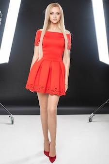 Belle femme confiante dans une robe rouge debout à la lumière de deux lampes de studio photo. concept de mode