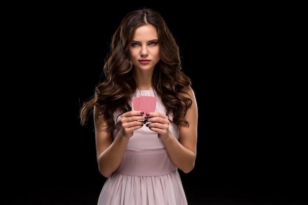Belle femme confiante montrant des cartes de poker en regardant la caméra avec lieu de copie