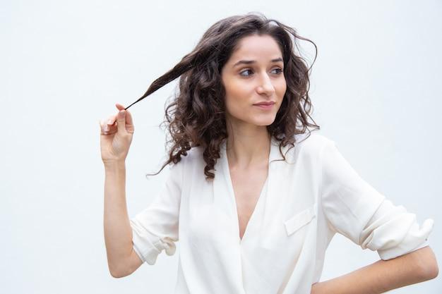 Belle femme confiante positive tenant une mèche de cheveux bouclés