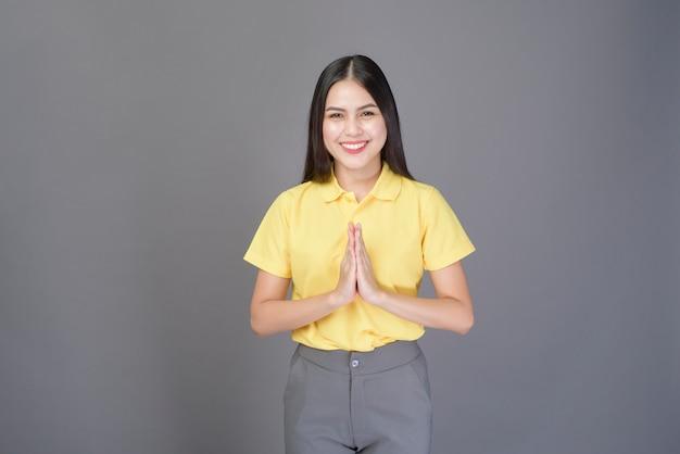 Belle femme confiante salue (thai wai) pour montrer son respect sur le gris