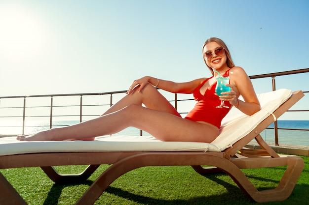 Belle femme avec un corps parfait se faire bronzer sur une chaise longue