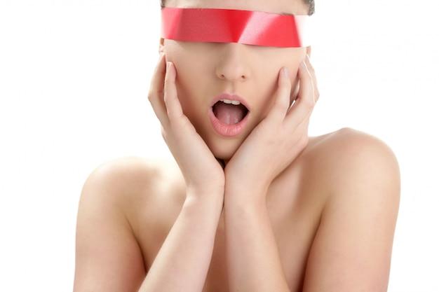 Belle femme cosmétique avec du ruban rouge dans les yeux