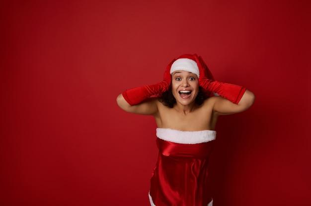 Belle femme en costume de carnaval de santa tient ses mains sur la tête et se réjouit en regardant la caméra, exprimant sa surprise, isolée sur fond rouge avec espace de copie pour l'annonce de noël et du nouvel an