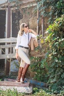 Une belle femme en costume d'équitation se reposant dans le grenier à foin