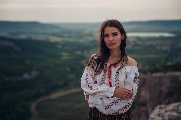 Belle femme en costume roumain traditionnel sur fond flou vert montagne