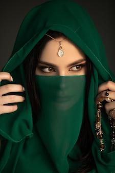 Belle femme en costume traditionnel. portrait élégant de jeune fille avec un maquillage lumineux parfait portant des bijoux traditionnels debout à l'intérieur sur fond sombre. le modèle regarde au loin