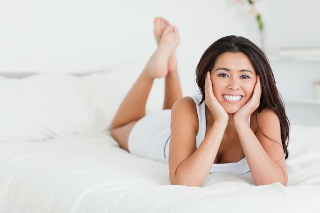 Belle femme couchée sur le lit avec les jambes croisées regardant dans la caméra