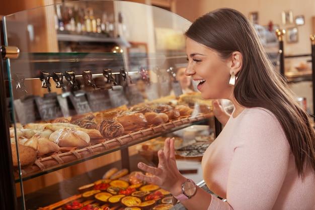 Belle femme courbée taille plus shopping pour la pâtisserie