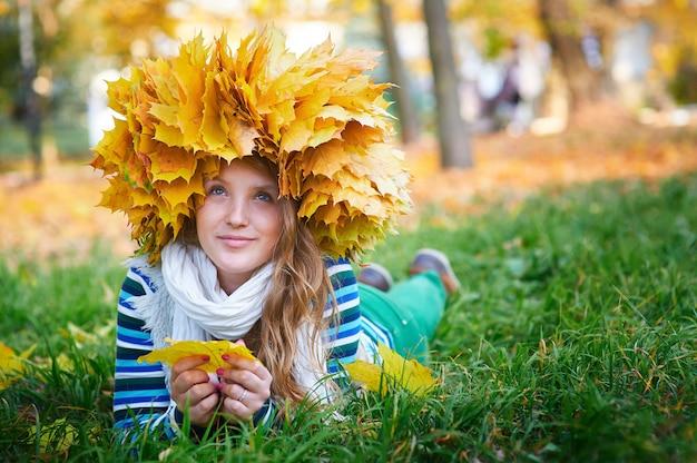 Belle femme avec une couronne de feuilles jaunes dans le parc