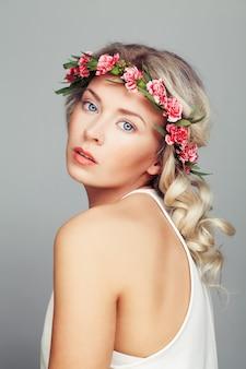 Belle femme avec une couronne de fleurs. coiffure blonde frisée et maquillage de mode
