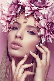 Belle femme avec une couronne de fleurs et de maquillage tenant la main sous son menton
