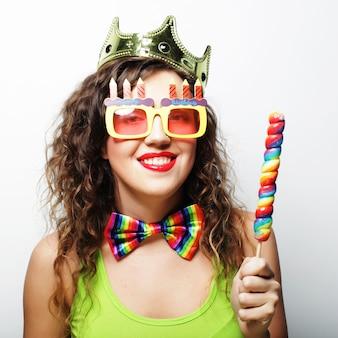 Belle femme avec une couronne et des lunettes de soleil drôles