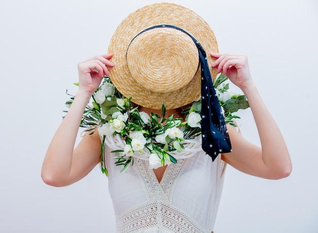 Belle femme avec une couronne de roses blanches sur fond blanc