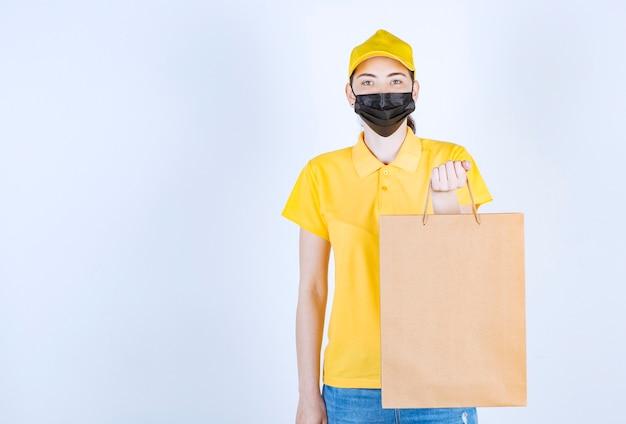 Belle femme courrier dans un masque tenant le sac dans sa main gauche devant le mur blanc