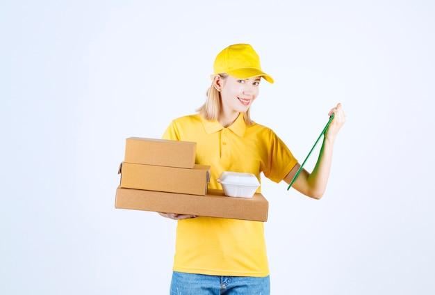 Belle femme courrier tenant son dossier comme s'il lisait et souriait tenant ses boîtes de nourriture