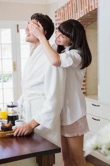 Belle femme couvrant les yeux de l'homme dans la cuisine