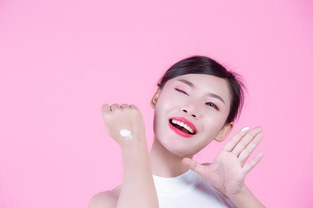 Belle femme avec de la crème sur la peau sur un fond rose.