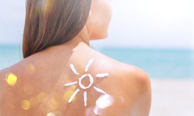 Belle femme avec crème solaire solaire sur fond d'océan. bronzage.