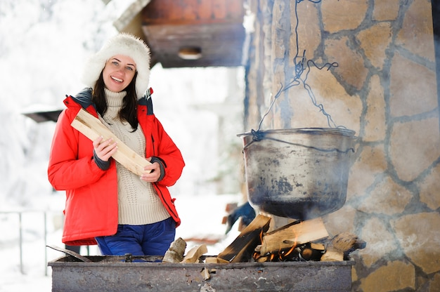 Belle femme cuisine dîner en plein air d'hiver.