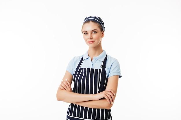Belle femme cuisinier en tablier rayé et casquette rêveusement