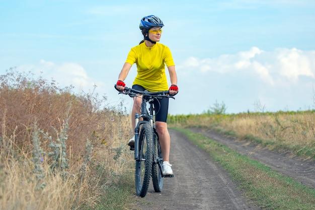 Belle femme cycliste monte sur le terrain à vélo =