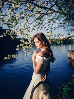 Belle femme dans les arbres de fleurs de printemps