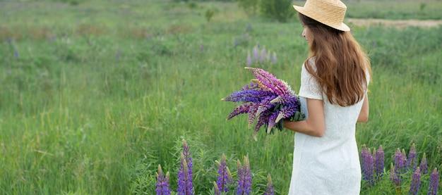 Belle femme dans la bannière de champ de lupin. jolie fille tenant un bouquet de lupins en robe blanche et chapeau