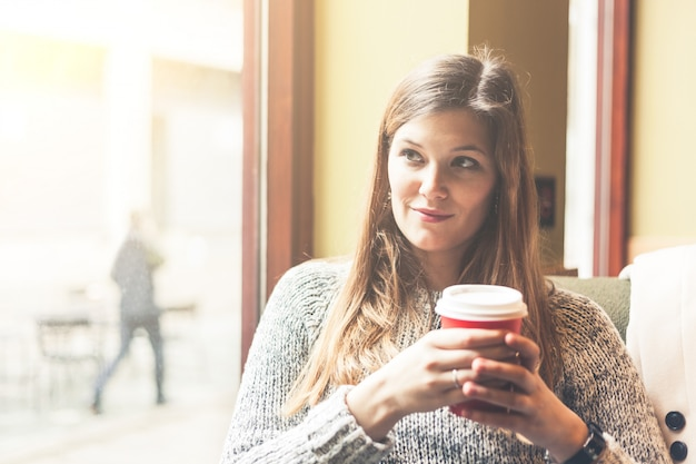 Belle femme dans un café tenant une tasse de thé