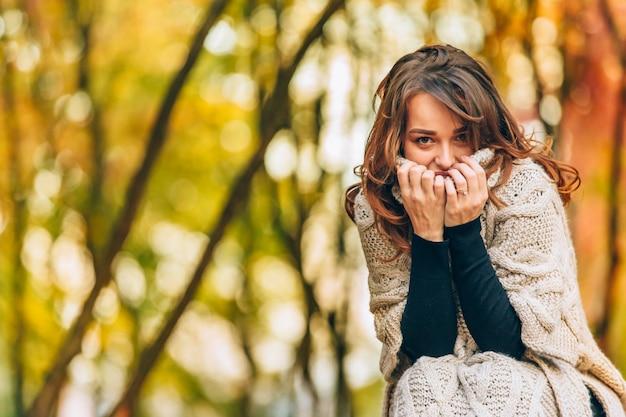 Belle femme dans un cardigan tricoté touche le col par ses mains dans le parc