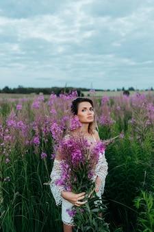 Belle femme dans un champ de fleurs roses