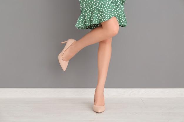 Belle femme dans des chaussures élégantes près du mur de couleur
