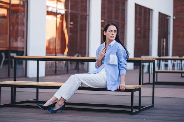 Une belle femme dans une chemise et un pantalon est assis sur un balcon